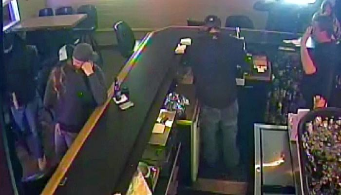 A couple at a bar, pictured to the left, looked up from their make-out session long enough to see robbers getting away. (Source: Surveillance footage/Billings Police Department/KTVQ/CNN)