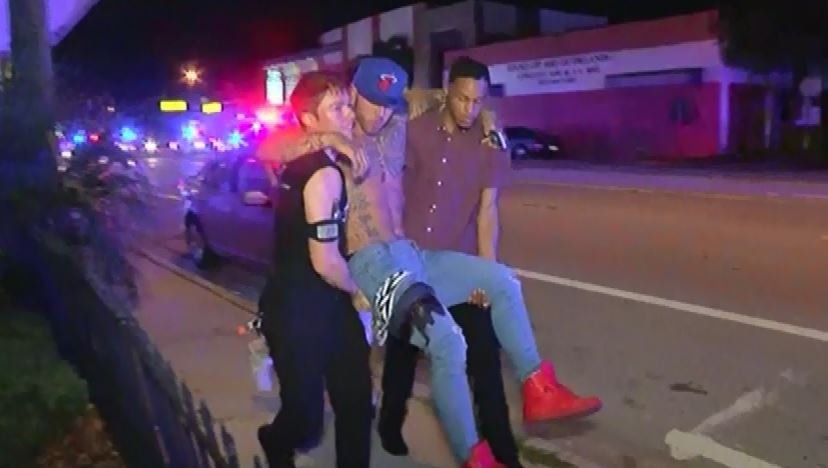 A shooting victim is carried away from the night club. (Source: WKMG/CNN)