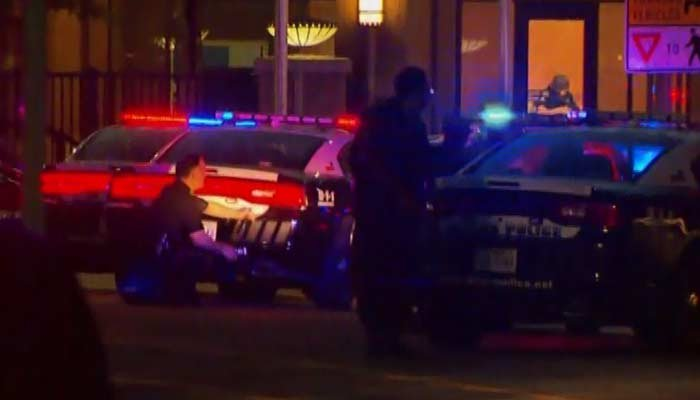 Police in Dallas take position after gunshots were fired at a protest. (Source: KTVT/CNN)
