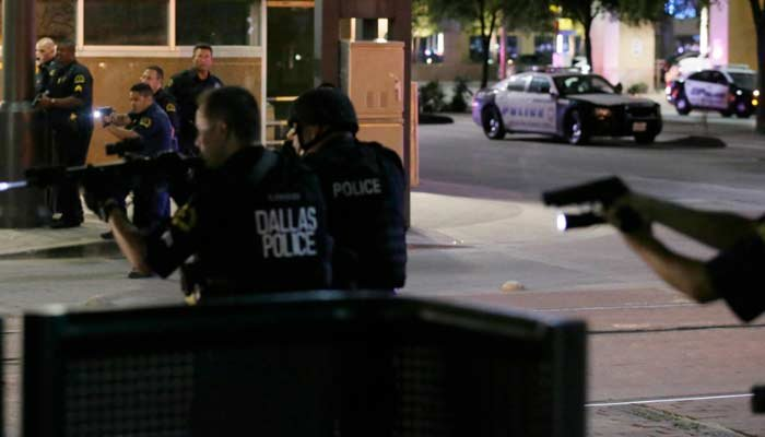 Dallas police move to detain a driver after several police officers were shot in downtown Dallas, Thursday, July 7, 2016. (Source: AP Photo/LM Otero)