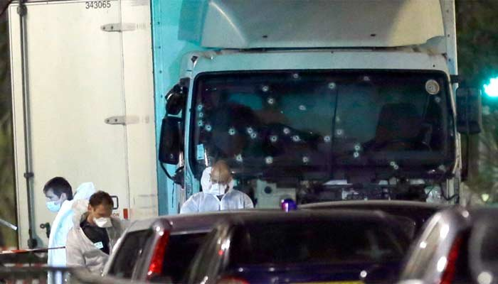 Forensic officers stands near a truck with its windscreen riddled with bullets, that plowed through a crowd of revelers who'd gathered to watch the fireworks in Nice, southern France, July 15, 2016. (Source: AP Photo/Claude Paris)