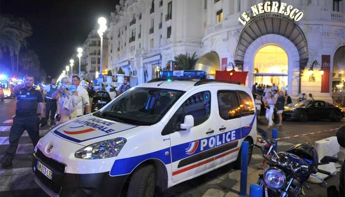 A Police car is parked near the scene of an attack after a truck drove on to the sidewalk and plowed through a crowd of revelers who'd gathered to watch the fireworks in the French resort city of Nice. (Source: AP Photo/Christian Alminana)