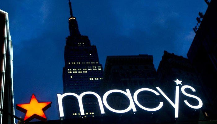 In this Nov. 21, 2013 photo, with the Empire State building in the background, the Macy's logo is illuminated on the front of the department store in New York. Macy's has about 730 stores.  (Source: AP Photo/Mark Lennihan)