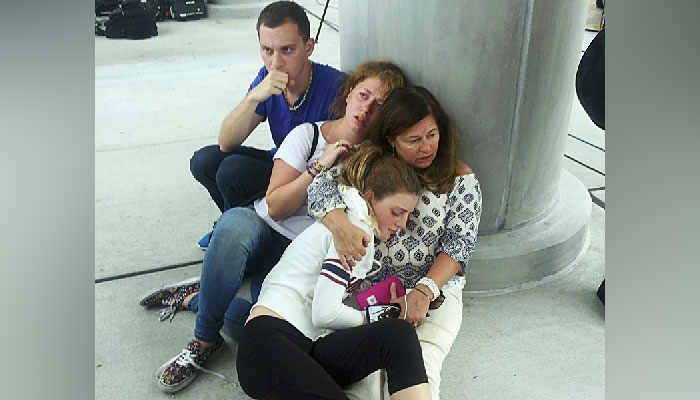 People hide at a pole at Fort Lauderdale-Hollywood International Airport Friday, Jan. 6, 2017, after a gunman opened fire in the baggage claim area at the airport.  (AP Photo/Julie Brown)