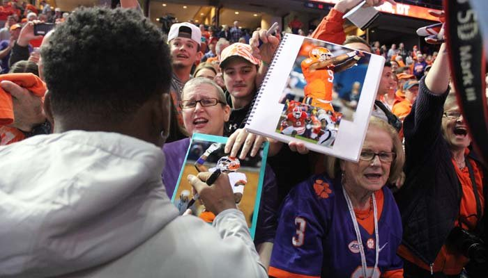 Clemson running back Wayne Gallman signs pictures for fans at media day for the College Football Playoff national championship. (Brian Tynes/Raycom Media)