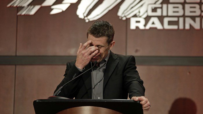 Carl Edwards wipes a tear as he speaks to the media about his decision to leave NASCAR. (Source: AP/Chuck Burton)