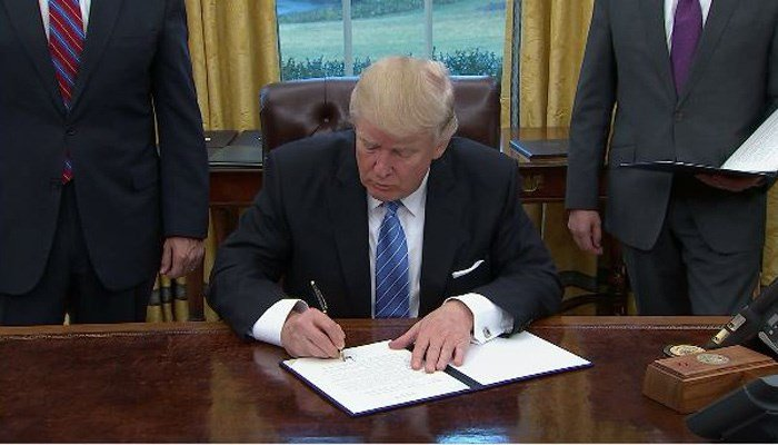 President Trump signs executive orders on Monday in the Oval Office. (Source: CNN)