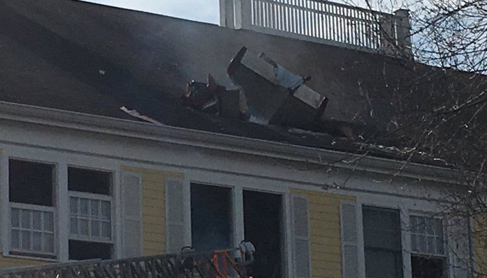 Crashed plane hoisted from roof of condo building