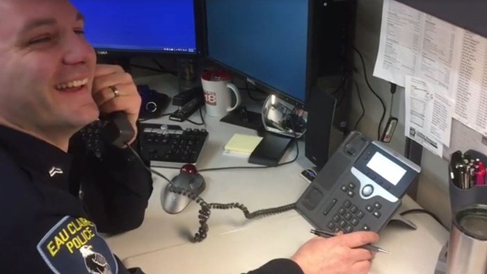 Officer Kyle Roder cracks up as he strings along a scammer claiming to be an IRS agent. (Source: Facebook/Eau Claire Police Dept.)