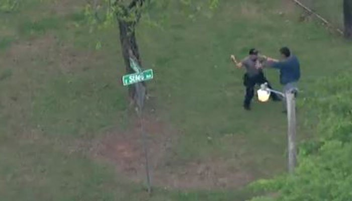 A suspect and an officer wrestle on Monday in an Oklahoma neighborhood. (Source: KFOR/CNN)
