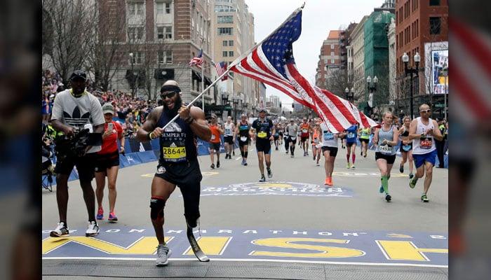 Jose Sanchez, of San Antonio, carries the United States flag across the finish line in the 121st Boston Marathon on Monday, April 17, 2017, in Boston. (Source: AP Photo/Elise Amendola)