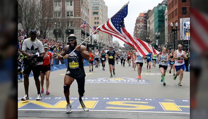 Jose Sanchez, of San Antonio, carries the United States flag across the finish line in the 121st Boston Marathon on Monday, April 17, 2017, in Boston. (Source: AP Photo/Elise Amendola)