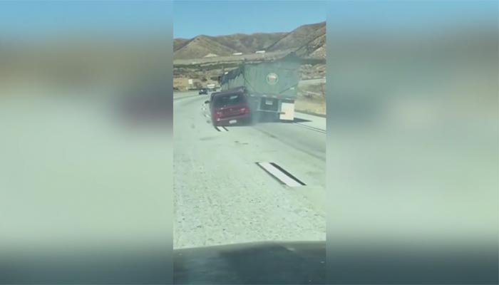 Insane  video shows auto  being dragged by truck driver on I-15