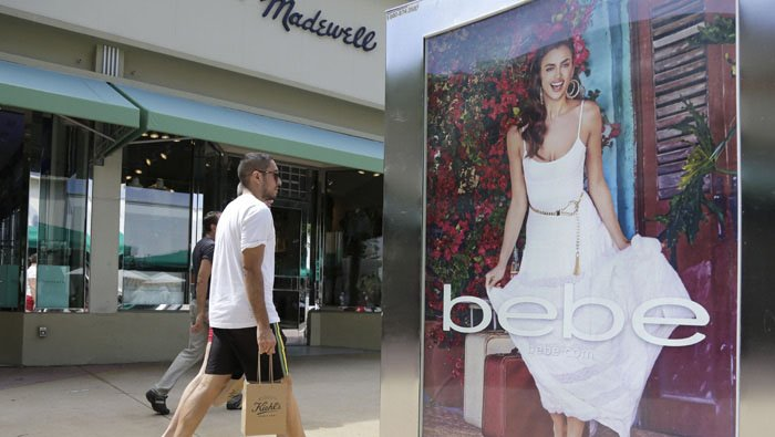 "In this March 13, 2015 photo, shoppers walk past an advertisement for retailer ""bebe"" along Lincoln Road Mall, a pedestrian street featuring retail stores and outdoor cafes, in Miami Beach, Fla.  (AP Photo/Lynne Sladky)"