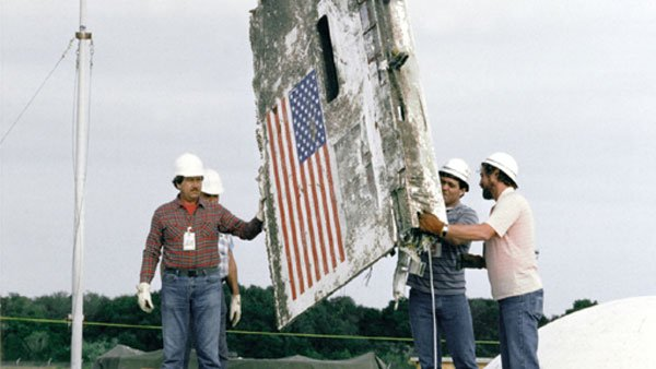 Crews carry a piece of the space shuttle Challenger, which exploded at 11:40 a.m. EST on Jan. 28, 1986. (Source: CNN)