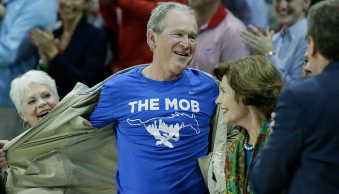 Former President George W. Bush opens his jacket to show off a T-shirt during the first half of an NCAA college basketball game between Cincinnati and SMU in Dallas, Sunday, Feb. 12, 2017. (Source:  AP Photo/LM Otero)