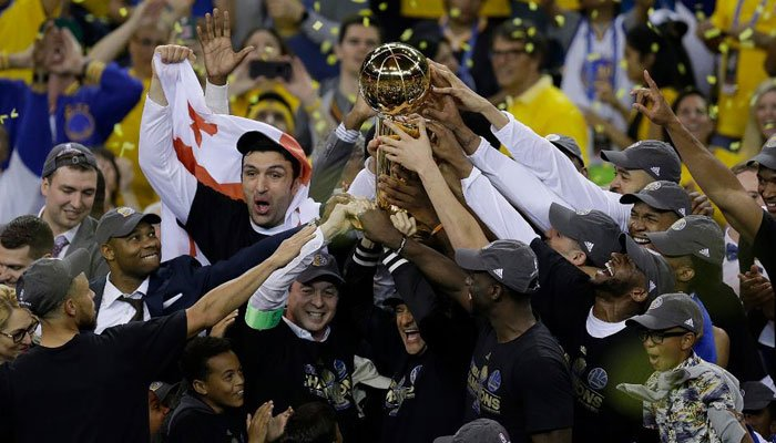 Golden State Warriors players, coaches and owners hold up the Larry O'Brien NBA Championship Trophy. (Source: AP Photo)