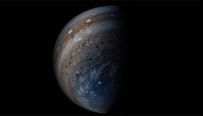 Jupiter appears draped in many different colorize in a photograph taken by Juna, a spacecraft launched by NASA. (Source: NASA)