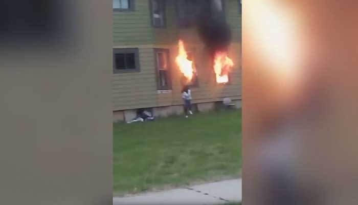Cell phone video posted live on Facebook shows a woman setting a house on fire, then escaping. A 72-year-old man died in the fire. (Source: WDJT/CNN/Dora Johnson)