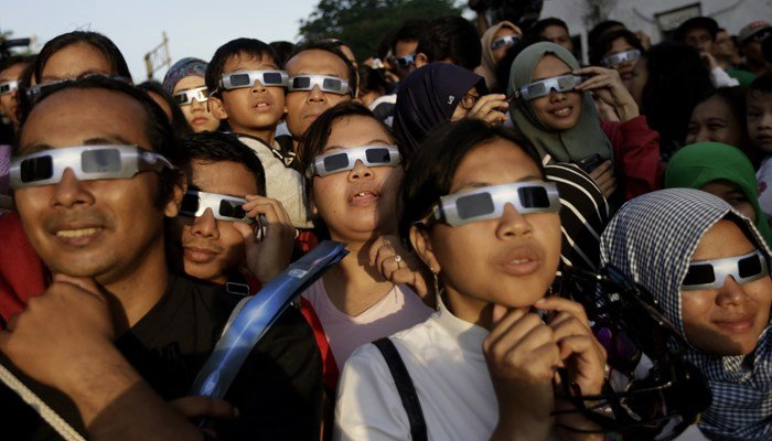 People wear protective glasses to watch a solar eclipse in Indonesia in March 2016.  (Source: AP/Dita Alangkara)
