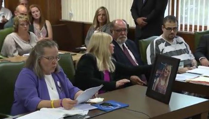 Leannda Bruck, at far left, the mother of the slain Chelsea Bruck, speaks as a Bible is passed to her daughter's killer on Thursday. (Source: WXYZ/Family photos/CNN)