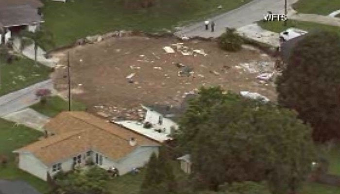 A sinkhole forced a neighborhood to evacuate Friday, as it opened underneath a home. The hole was initially the size of a small swimming pool, AP reports, but now has started to swallow two large single family homes. (Source: WFLA/CNN)