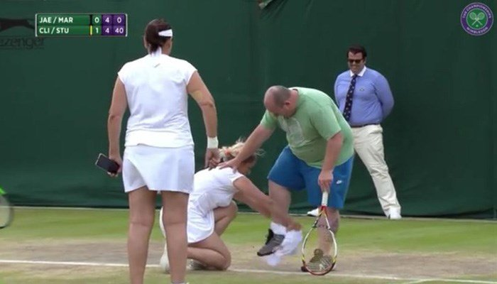 Kim Clijsters fits a fan with dress cord-conforming attire before letting him take a couple of serves. (Source: Wimbledon/YouTube)
