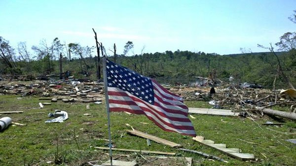 A debris-littered yard shows signs of hope with an American flag. (Source: WBRC)