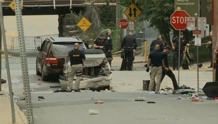 Police crowd around a car that drove into a group of pedestrians. (Source: CNN)