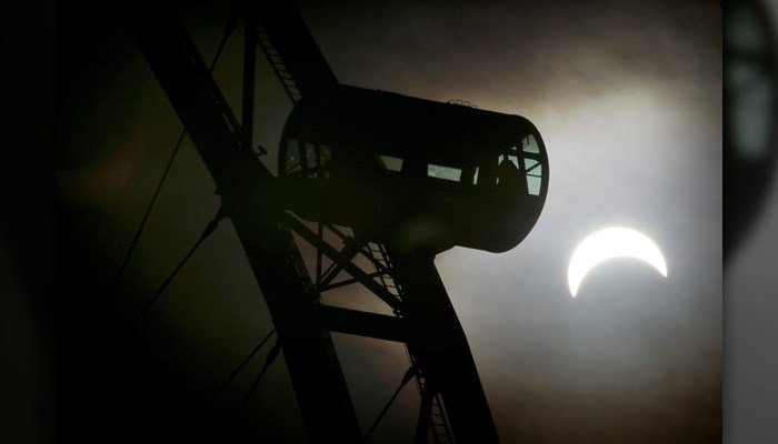 A partial solar eclipse is seen behind a passenger capsule of the Singapore Flyer March 9, 2016, in Singapore. (AP Photo/Wong Maye-E)