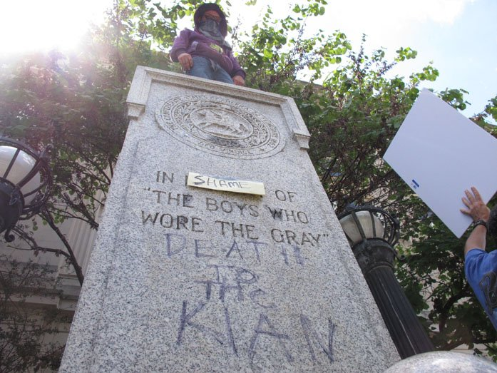 A protester looks down from where a Confederate statue once stood in front of the old Durham County Courthouse in Durham, NC, on Friday. Protesters pulled the statue down on Monday and came back to deface the pedestal on Friday. (AP Photo/Allen G. Breed)