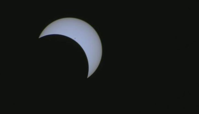 A crecent sun hangs over the midday sky. (Source: CNN)
