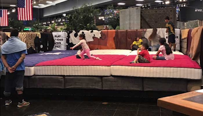 "Kids play on mattresses  in the Gallery Furniture store in Houston. Two of  Jim ""Mattress Mack"" McIngvale's stores opened their doors to people left temporarily homeless by Tropical Storm Harvey's floodwaters. (Source: CNN/Jim McIngvale)"