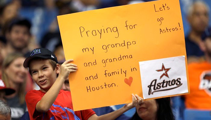 A young fan holds up a sign during the MLB game between the Houston Astros and the Texas Rangers in St. Petersburg, FL, on Aug. 28. The Astros moves their three-game home series to St. Petersburg because of floods. (Source: AP/ C. O'Meara)