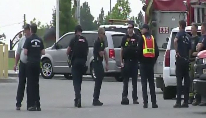 Police secure the perimeter of a high school in Spokane, WA after a shooting that killed one person and injured others. (Source: KXLY/CNN)