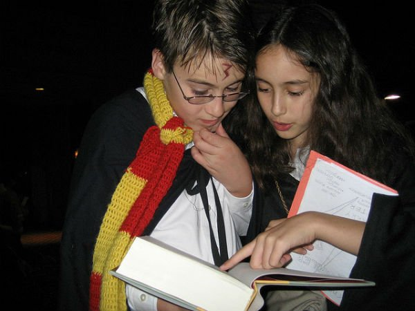 Two siblings pore over the last Harry Potter book, Harry Potter and the Deathly Hallows, at a release party in 2007. (Source: pilgrimgirl/Flickr)