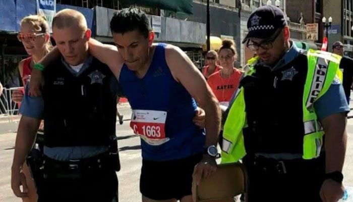 After a runner's hip broke in the last few miles of the race, two police officers stepped up to help him cross the finish line. (Source: Edward Hensley/WBBM/CNN)