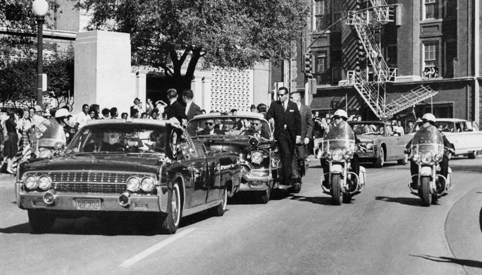 "In this Nov. 22, 1963 photo, seen through the foreground convertible windshield, President Kennedy's hand reaches toward his head within seconds of being fatally shot as the first lady holds his forearm. (Source: AP Photo/James W. ""Ike"" Altgens, File)"