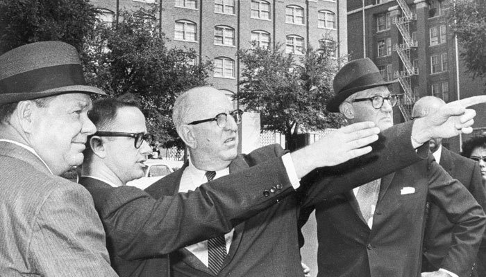 Members of the Warren Commission investigating President John F. Kennedy's assassination, visited Dallas on Sept. 6, 1964. In the background is the Texas School Book Depository Building, where the deadly shots were fired. (Source: AP Photo/Ferd Kaufman)