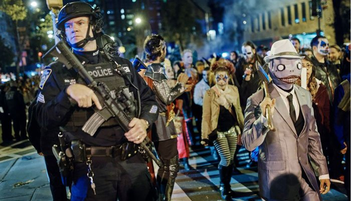 Heavily-armed police guard as revelers march during the Greenwich Village Halloween Parade, Tuesday, Oct. 31, 2017, in New York. New York City's always-surreal Halloween parade marched under the shadow of a terror attack. (Source: AP Photo/Andres Kudacki)