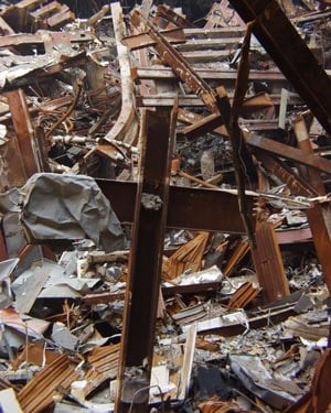 Piles of rubble and debris are all that remain of the 110-story twin towers of the World Trade Center and several of its neighboring buildings. In Building 6, firefighters have found pieces of the towers that resemble crosses. (Source: Mike Rieger/FEMA)