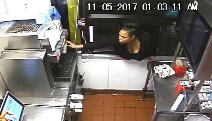The woman in the video reaches through what looks like a drive-through window  to get a drink.  (Source: Howard County Police Department)