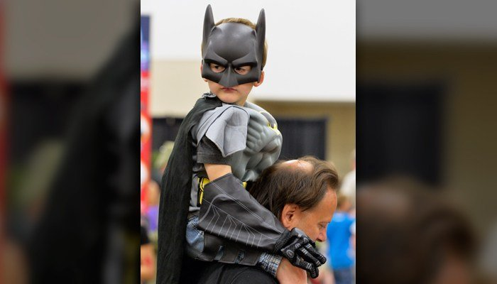 Logan Wise, 4, dressed as Batman, rides on his father Frank's shoulders at the Derby City Comic Con in Louisville, KY, June 20, 2015. Dressing up may work wonder's for kids' perserverance. (AP Photo/Timothy D. Easley)