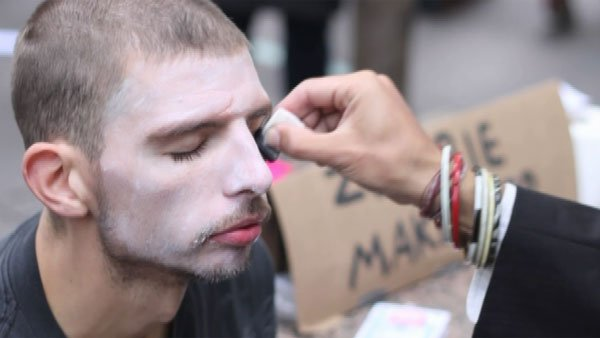 "Protesters received ""zombie makeovers"" Monday for a demonstration against corporate greed. (Source: CNN)"