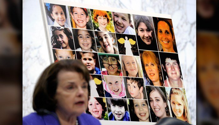 In this Feb. 27, 2013, file photo faces of Sandy Hook Elementary School victims are seen behind Sen. Dianne Feinstein, D– CA, as she speaks about the Assault Weapons Ban of 2013 during the Senate Judiciary Committee on Capitol Hill. (AP Photo/Susan Walsh)