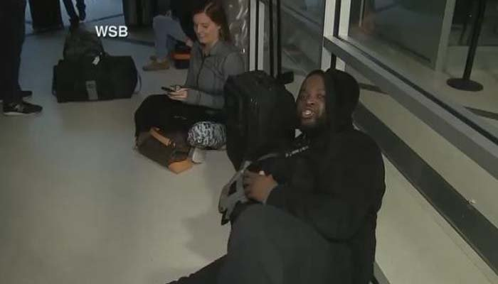 Passengers sit in the terminal waiting for the power to be restored. (Source: WSB via CNN)