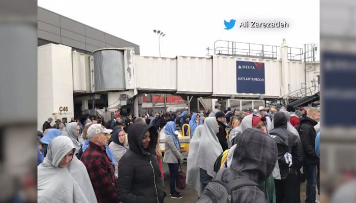 Passengers stand outside in the cold after being evacuated from the airport. (Source: Ali Zarezadeh/Twitter)