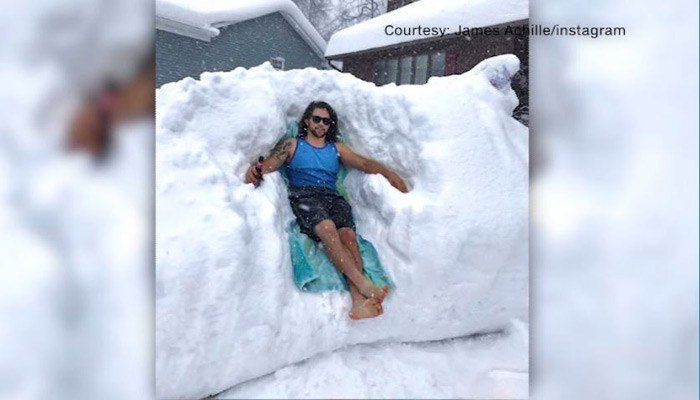 James Achille lounges in 5 feet of snow in his driveway in Millcreek Township, PA. (Source: James Achille/Instagram)