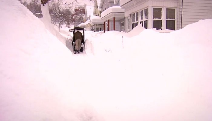 A Syracuse, NY, man works to dig out of the snow on Wednesday. (Source: WSYR/CNN)