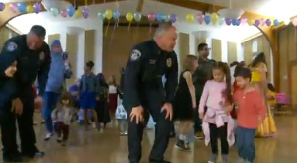 The girls also got quite a laugh watching their dads, firefighters and officers in a hula hooping contest. (KSTU/CNN)